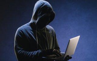 hooded laptop user